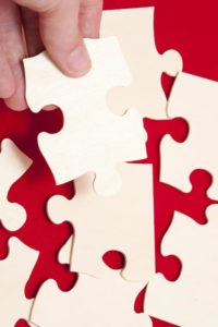 person's hand placing a jigsaw puzzle piece
