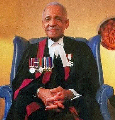 Judge Grizzle sits in a blue wing chair wearing his judges robes and medals.