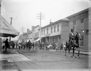 Man on horse leading parade through street.